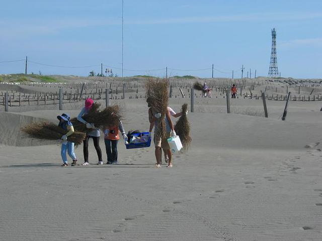 IMG_0474扛著竹枝籃框往沙洲前進_背景是台灣最西端國聖燈塔.JPG